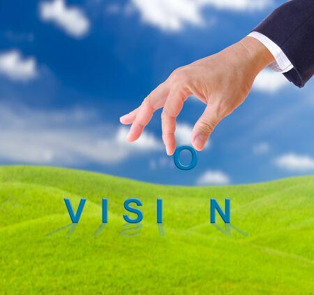 zakenman hand en visie woord op groen gras weide