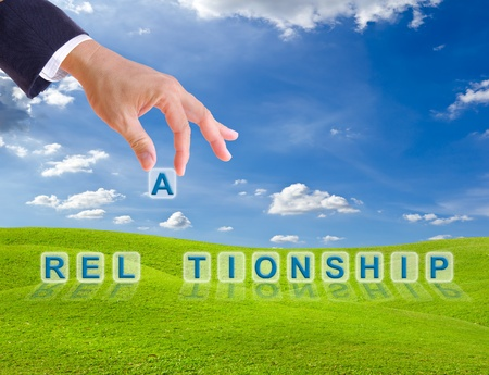 business man hand and relationship word buttons on green grass meadow Stock Photo - 9943552