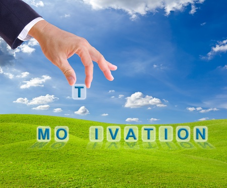 improvement: business man hand made motivation word buttons on green grass meadow Stock Photo