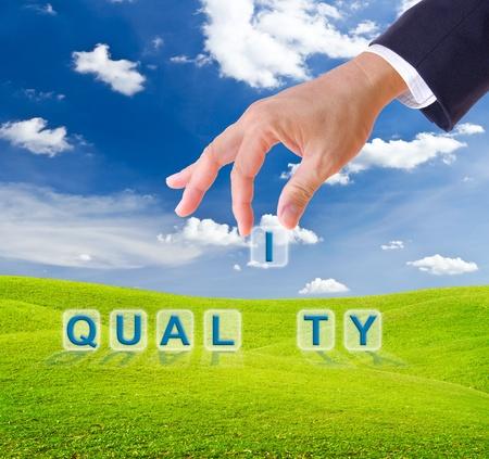zakelijke man hand gemaakt kwaliteit woord knoppen op groen gras weide Stockfoto