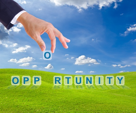 business man hand made opportunity word buttons on green grass meadow