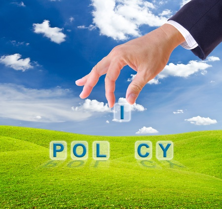 government: business man hand made policy word buttons on green grass meadow Stock Photo
