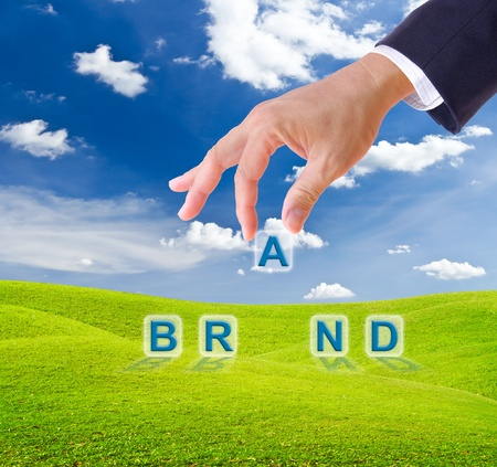 business man hand made brand word buttons on green grass meadow Stock Photo - 9943547