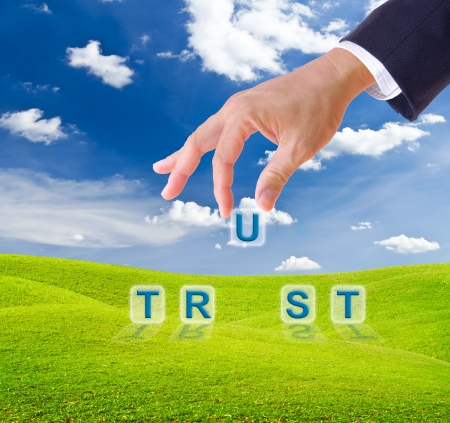 intuition: business man hand made trust word buttons on green grass meadow