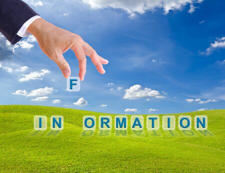 business man hand made information word buttons on green grass meadow Stock Photo - 9943553