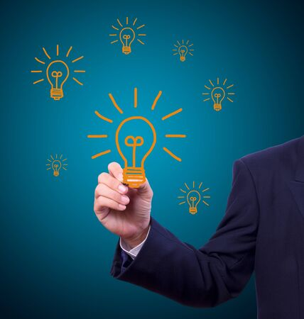 Hand with pen drawing light bulb Stock Photo - 10454620