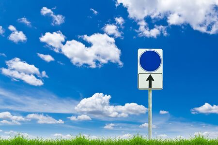 blue blank sign on fresh spring green grass against blue sky photo