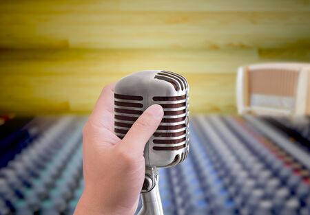 hand holding microphone in sound record room Stock Photo - 10750654