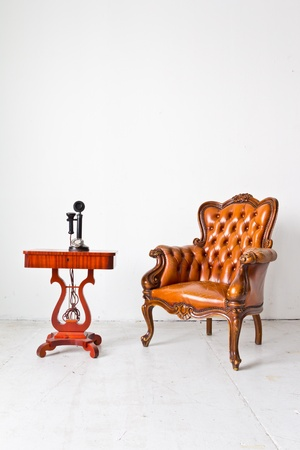 leather armchair: vintage luxury armchair and telephone in white room