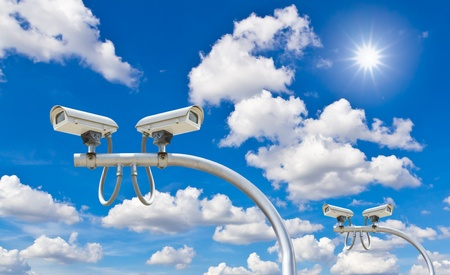 security search: outdoor security cctv cameras against blue sky and sunshine Stock Photo