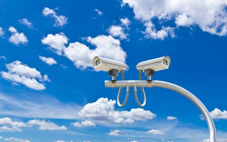 surveillance cameras against blue sky Stock Photo