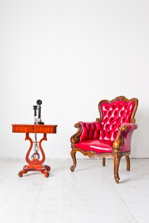 old sofa: vintage red luxury armchair and telephone in white room
