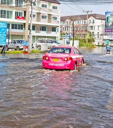 Bangkok-Nov 08 : Taxi drives in water flood road. Nov 08, 2011, Thailand , Bangkok, panya road and prayasuren road intersection