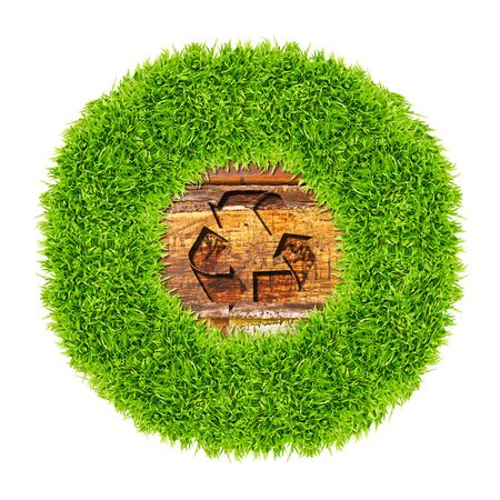 recycle sign and green grass on wood background photo