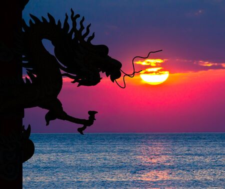 Dragon silhouette and sunset in the sea photo
