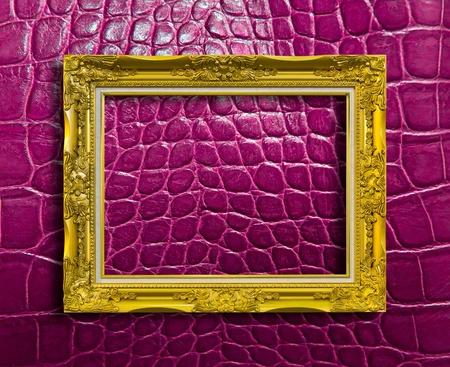 cadre de bois doré sur le cuir de crocodile violet avec chemin de détourage