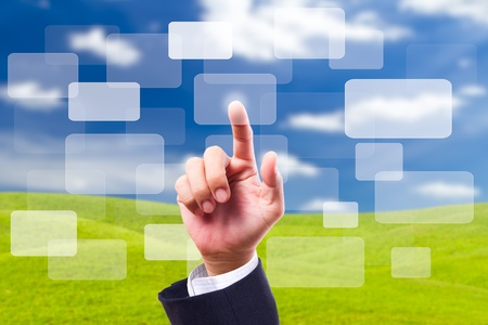 HAND pushing button on blue sky background photo