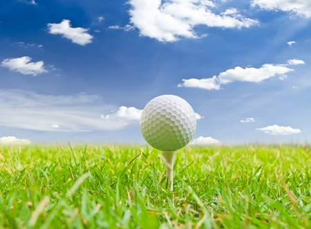 golf ball and tee grass against blue sky photo