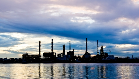 Silhouette Oil refinery plant at morning along river in Bangkok