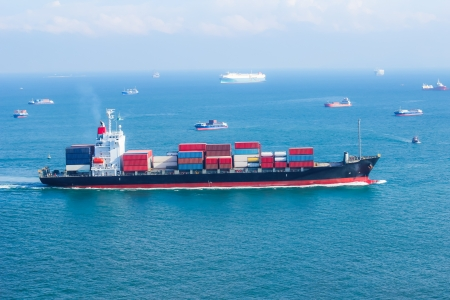 international shipping: cargo ship with containers sailing on the sea