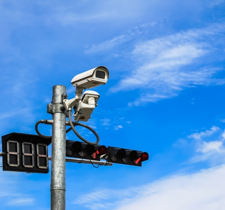 surveillance camera and traffic light against blue sky photo