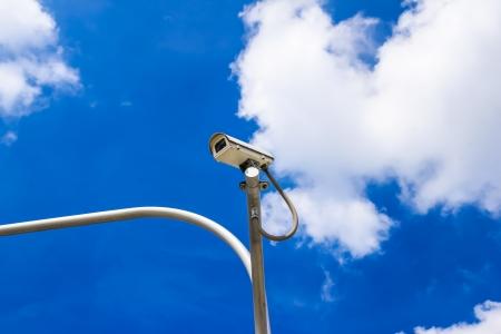 surveillance camera against blue sky photo