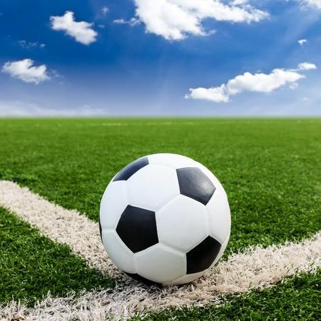 conner: soccer football on green grass field conner against blue sky