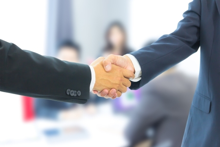 business man shaking hands with business people in meeting room photo