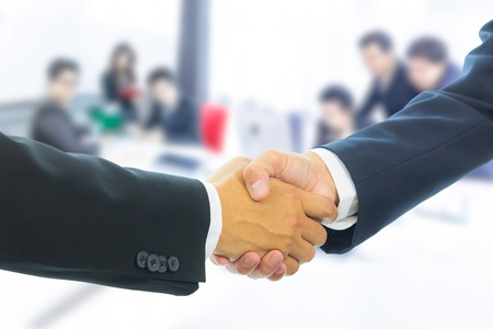 business man shaking hands with business people background photo