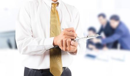 zakenman schrijven op clip breed met zakelijke mensen achtergrond Stockfoto