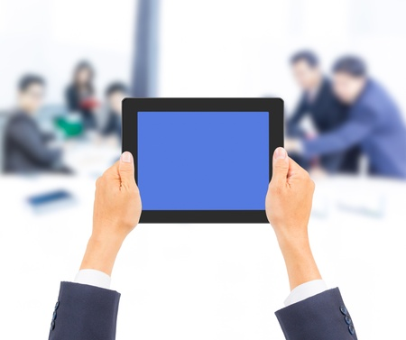 hand holding tablet PC with business people background photo