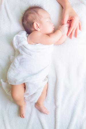 slapende baby met moeder de hand