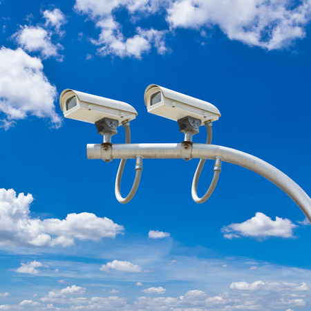 surveillance cameras against blue sky photo