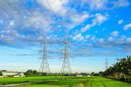 torres de alta tension: electricidad de alta tensión de la torre en el campo de arroz Foto de archivo