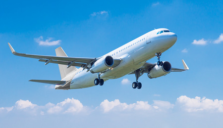 Commercial plane taking off against blue sky Stock Photo