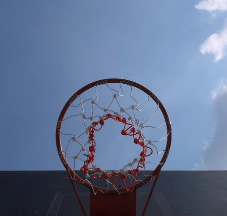 rim: Basketball hoop under the sky before noon.