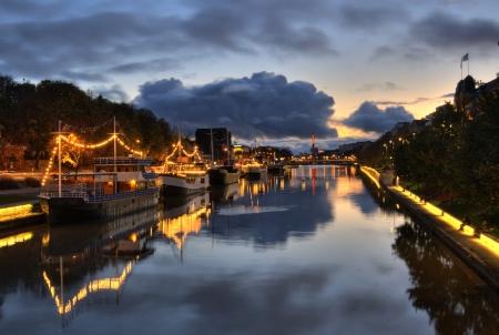 Boats in River Aura, Turku, Finland, at sunset. Фото со стока