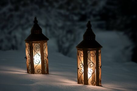 Candles burning in two lanterns on a snowy ground photo