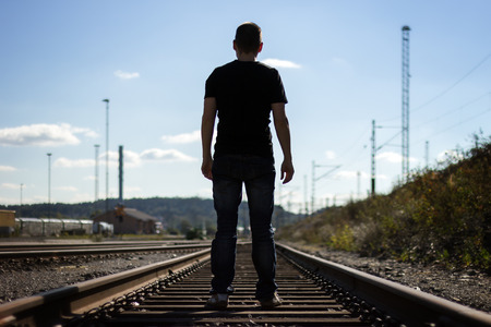 Silhouette of a man from behind standing on railway tracks