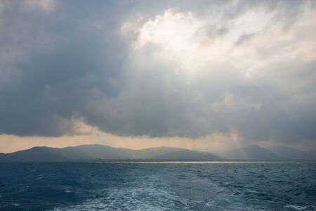'koh samui': Sunbeams through hole in the clouds above ocean, and silhouette of hilly Koh Samui, Thailand