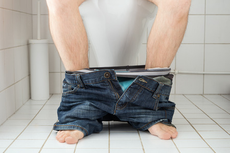 asiento: Hombre sentado en un asiento de inodoro con los pantalones y los calzoncillos abajo