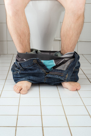 pants down: Man sitting on a toilet seat with his pants and boxers down