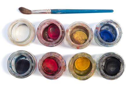 viewed: A brush and used watercolors in small glass jars isolated on white background, viewed from above