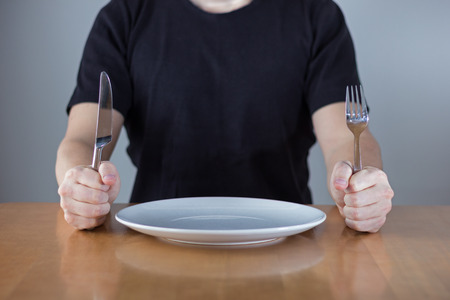 An unrecognizable man wearing black shirt sitting at a table in front of an empty plate waiting for food, holding fork and knife in his hands.