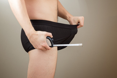 penis: Adult man pulling his black boxers with a tape measure in other hand. Concept photo of male sexuality, manhood and insecurity of penis size.
