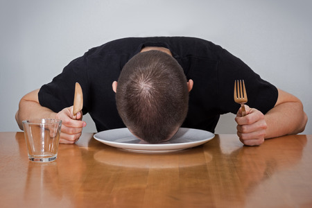 tired person: An unrecognizable man holding fork & knife, sleeping head on a plate on a table, tired of waiting for food Stock Photo