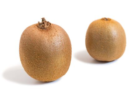 farther: Closeup of two kiwifruits (also known as kiwi or Chinese gooseberry) isolated on white background. The other one is slightly farther back and blurry.