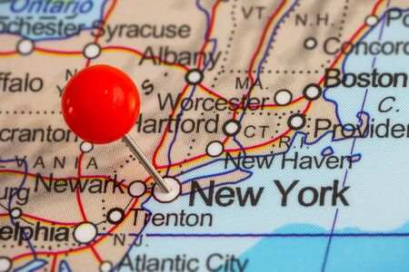 paper pin: Closeup of a red pushpin in a map of New York