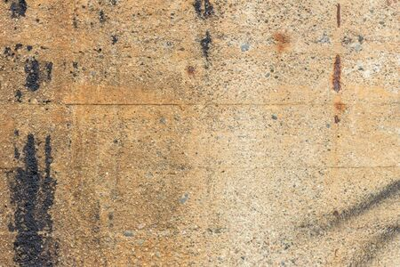 grimy: Close-up of a dirty pale brown concrete wall with spray paint and smudges