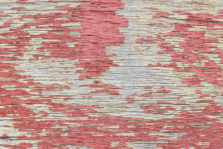 peeled off: Close-up of a cracked and weathered plywood texture background with red paint peeled off.
